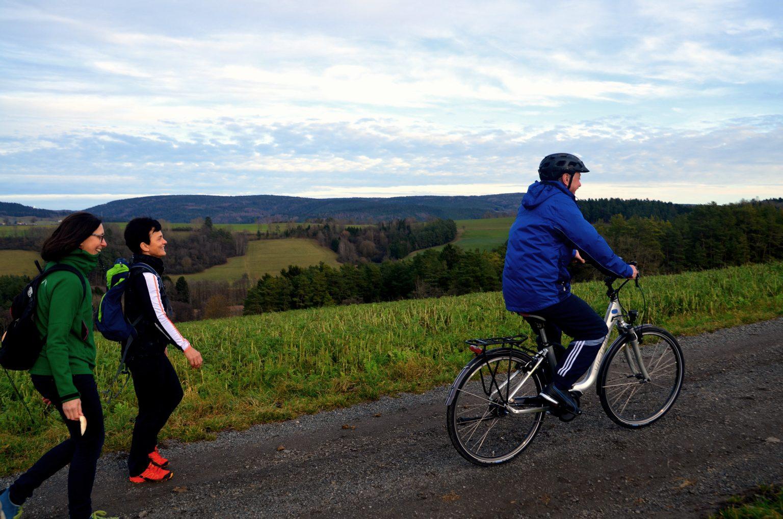 2 Wanderer begleiten einen Radfahrer auf einer Tour
